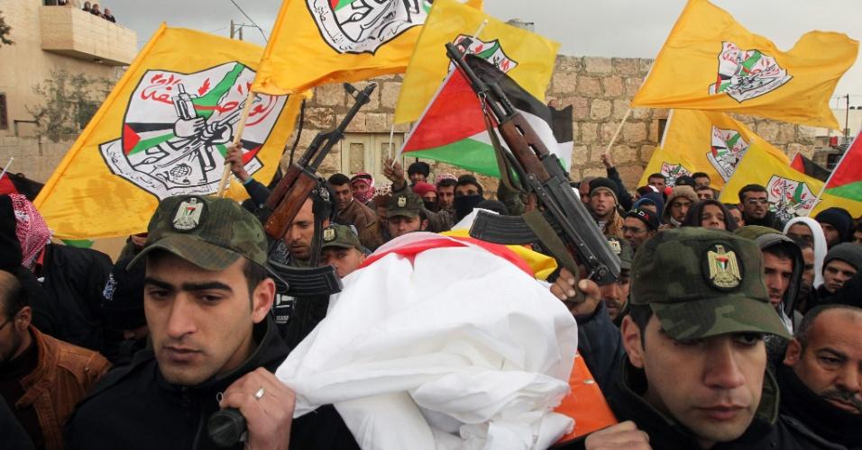 24.jan.2016 - Forças de segurança da Palestina carregam corpo de Roqaya Abu-Eid, adolescente de 13 anos morta por soldados israelenses após supostamente tentar realizar um ataque com uma faca no vilarejo de Yatta. O funeral da jovem contou com bandeiras nacionais, do partido Fatah e armas