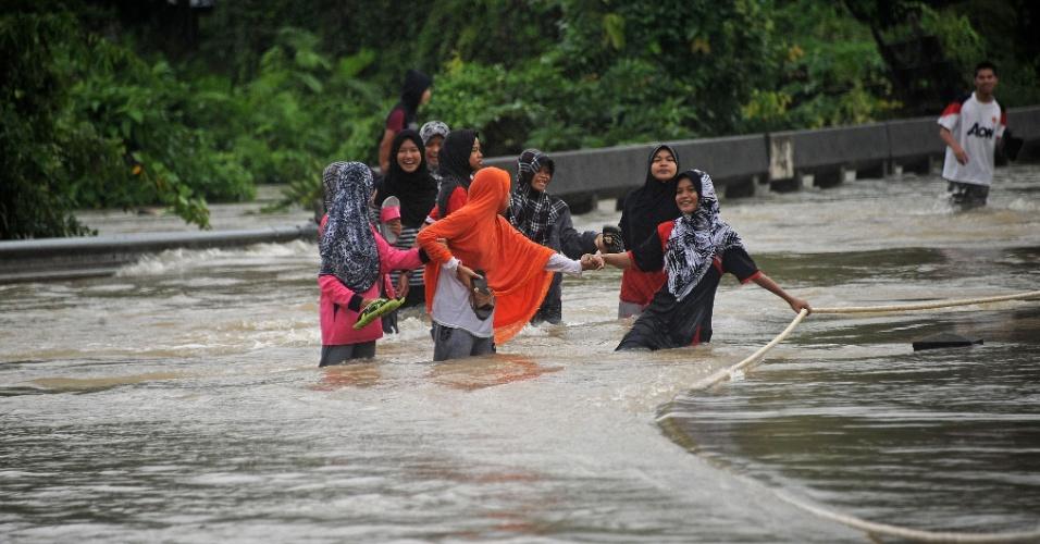 28.jan.2016 - Tailandesas caminham por área inundada após chuvas pesadas provocarem alagamentos em Rangae, no sul da Tailândia