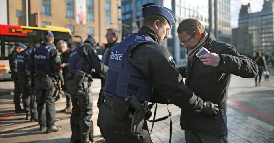 22.mar.2016 - Policial revista pedestre na região da estação Midi, em Bruxelas, Bélgica, após os atentados terroristas a capital belga nesta terça-feira