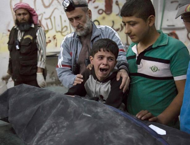 Menino chora ao lado de corpo de parente morto em ataque a hospital em Aleppo, na Síria