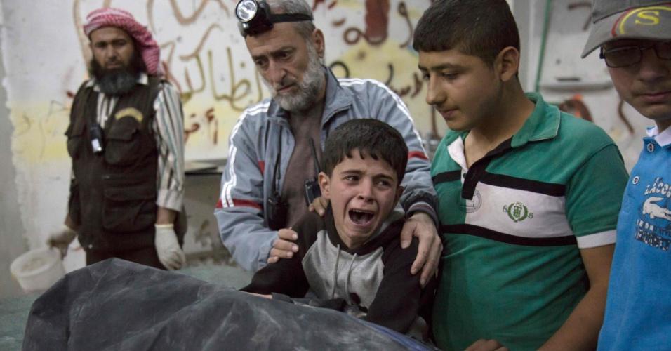 27.abr.2016 - Menino chora ao lado de corpo de parente morto em ataque a hospital em Aleppo, na Síria
