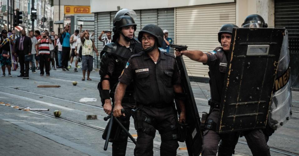 9.fev.2017 - Policial militar aponta revólver durante confronto com manifestantes em protesto de servidores públicos no centro do Rio, próximo à Alerj