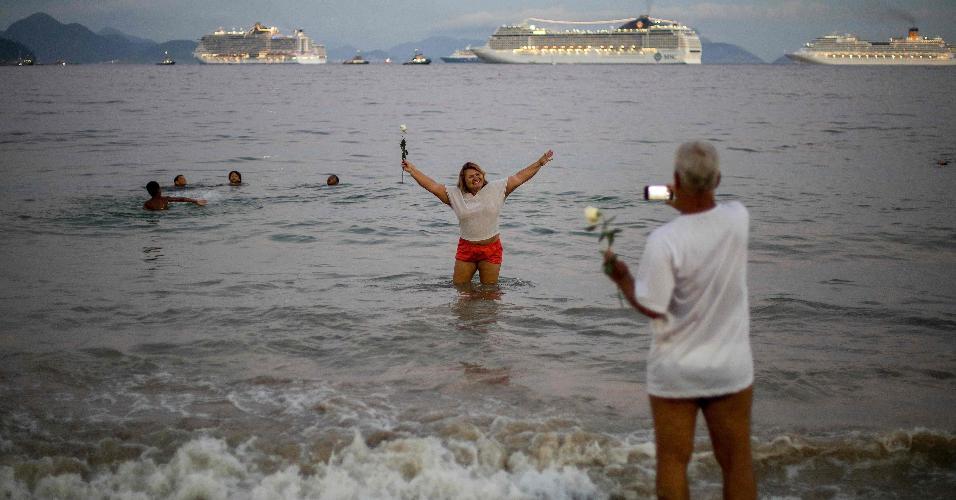 Com cruzeiros ao fundo, mulher posa para foto na praia de Copacabana, nos últimos minutos de 2018