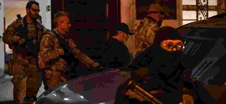 """De boné, no centro da imagem, Nicola Assisi, apontado como líder da máfia italiana """"Ndrangheta, ao ser preso, na Praia Grande, litoral de SP - 08.jul.2019 - Jota Erre/Agência O Dia/Estadão Conteúdo"""