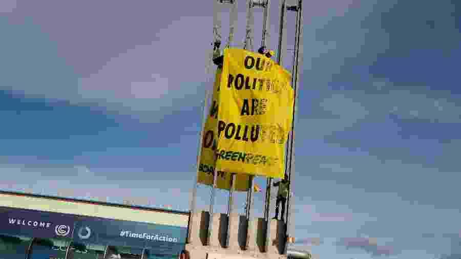"""Faixa é pendurada do lado de fora do prédio da ONU onde acontece a Conferência sobre Mudanças Climáticas, em Madri. No protesto, se lê """"Nossa política está poluída"""". - Reuters"""