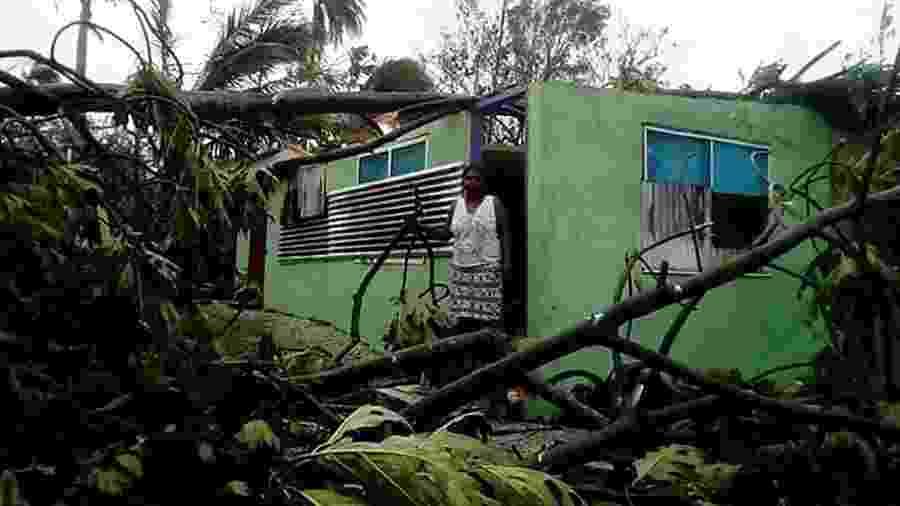 Moradora de uma casa danificada pela passagem do ciclone Harold em Vanuatu, também no Pacífico Sul - O. UMUUMULOVO/AFP