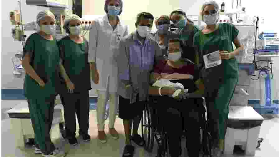 Lurdyani, na cadeira de rodas, ao lado do marido e da equipe médica, pega a filha no colo pela primeira vez, 51 dias depois do parto - Divulgação