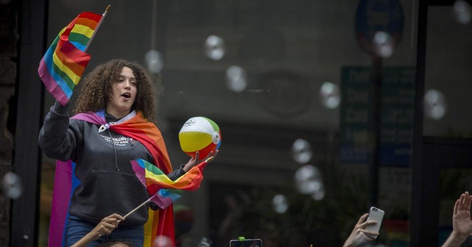 28.jun.2015 - Mulher segura uma bandeira de arco-íris durante a Parada do Orgulho Gay, ao longo da 5ª Avenida, em Manhattan, na cidade de Nova York (EUA), neste domingo (28). Uma decisão da Suprema Corte dos Estados Unidos legalizou na sexta-feira (26) o casamento entre pessoas do mesmo sexo, ao derrubar vetos estaduais à união homossexual