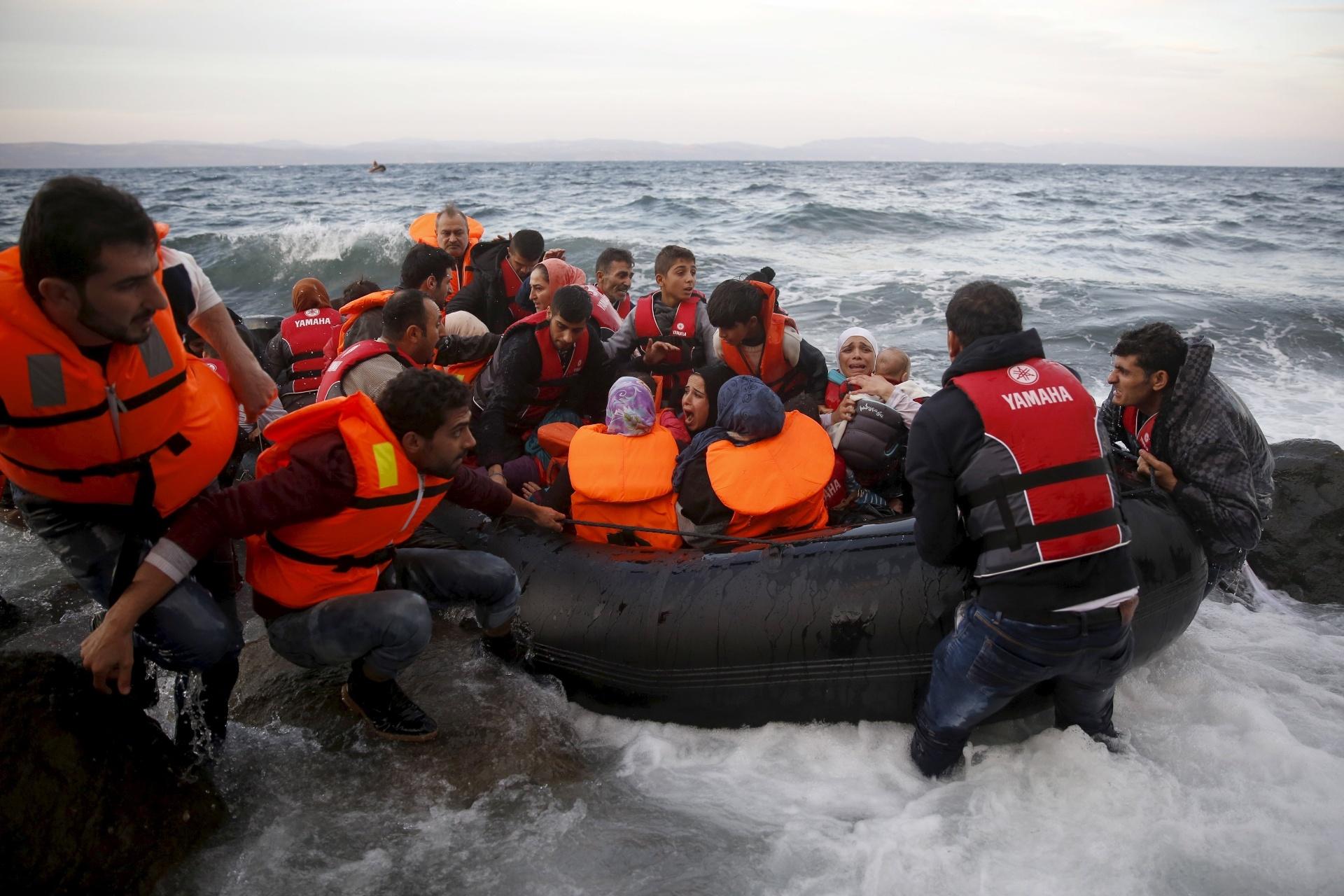 27.out.2015 - Refugiados sírios chegam em uma jangada, no mar agitado, em uma praia na ilha grega de Lesbos. Durante o mês de outubro, a chegada de refugiados e imigrantes através do mar Mediterrâneo à Europa superaram as registradas em qualquer mês anterior, com 179.470, disse nesta terça-feira (27) a Acnur (Agência das Nações Unidas para os Refugiados)