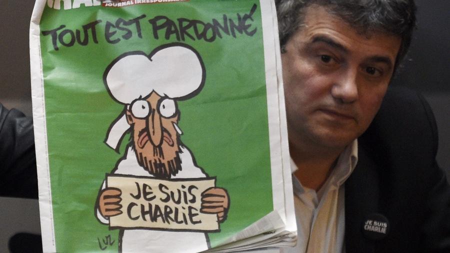 """Patrick Pelloux, ex-colunista da """"Charlie Hebdo"""" mostrando a capa da revista logo após o atentado de janeiro de 2015 - Martin Bureau/AFP"""