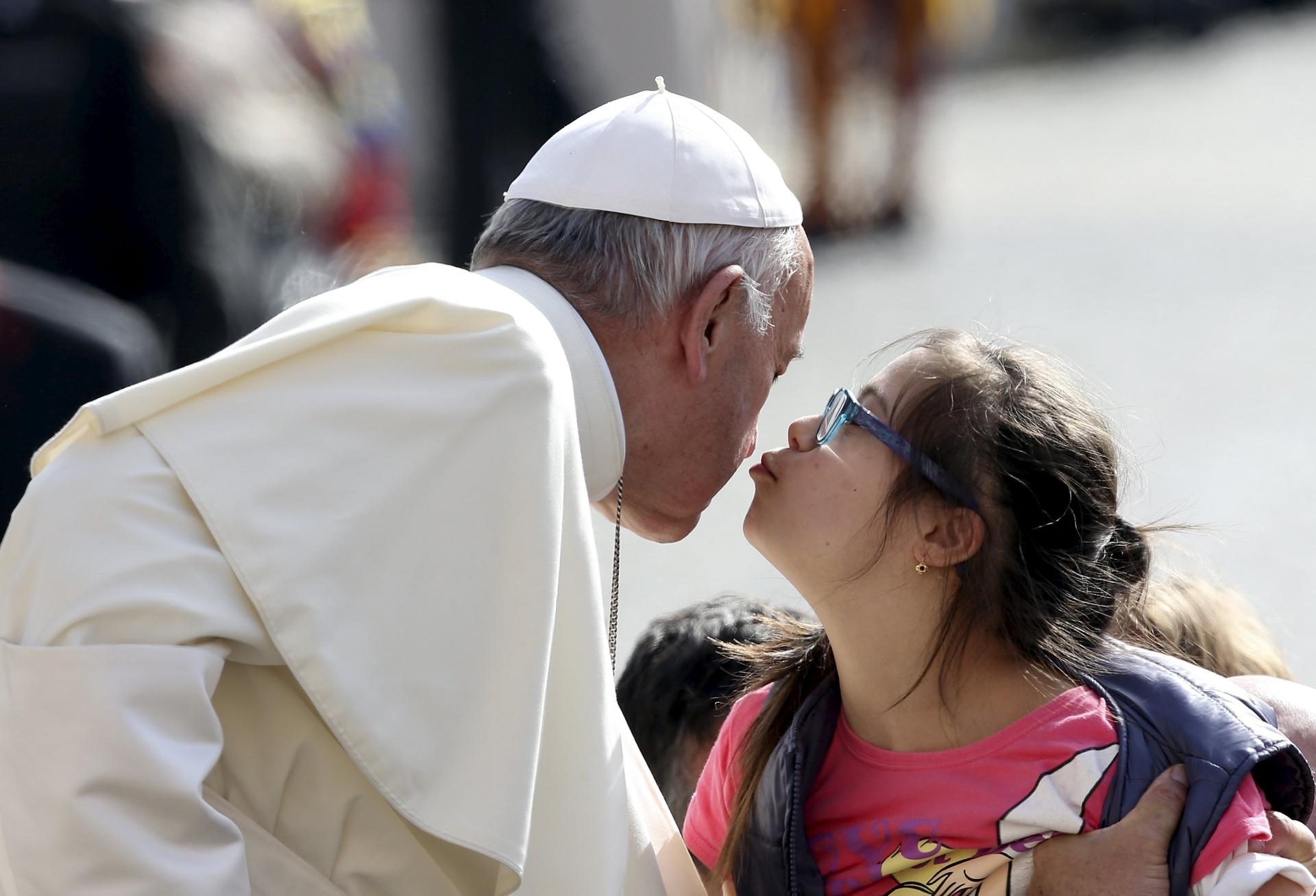6.abr.2016 - Papa Francisco recebe um beijo de uma criança durante a sua chegada para a audiência semanal na Praça de São Pedro, no Vaticano