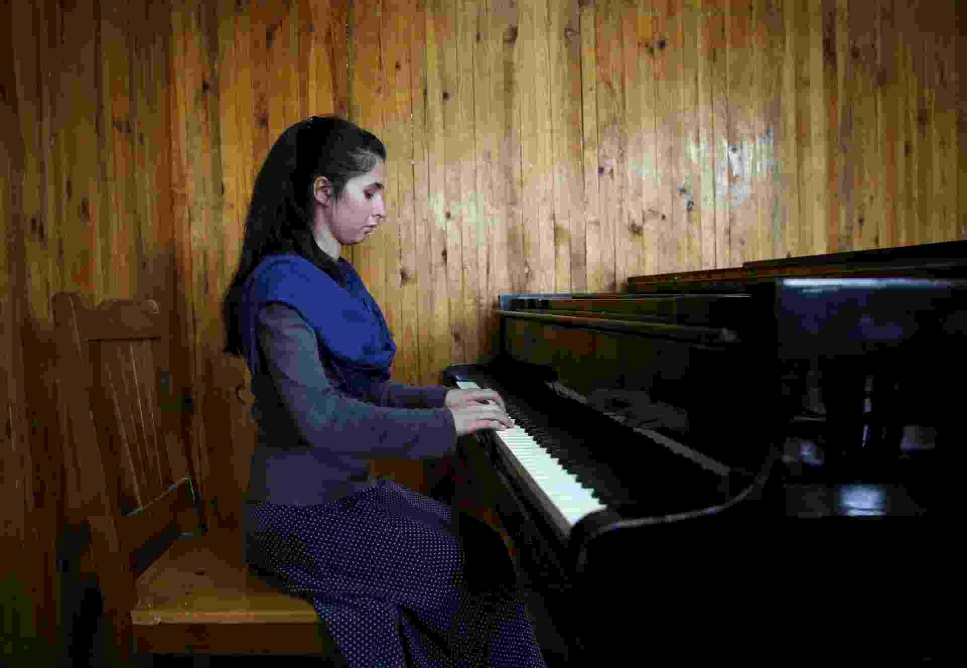 18.abr.2016 - Negin Ekhpulwak tem 19 anos e já lidera uma orquestra composta por 35 mulheres, em Cabul, no Afeganistão. É ela quem toca piano nessa foto tirada no dia 9 de abril no Instituto Nacional de Música do Afeganistão, que fica na capital afegã. No país, a atividade musical foi banida durante muitos anos durante o regime do Talibã e muitos muçulmanos conservadores desaprovam a maioria das formas de música - Ahmad Masood/Reuters