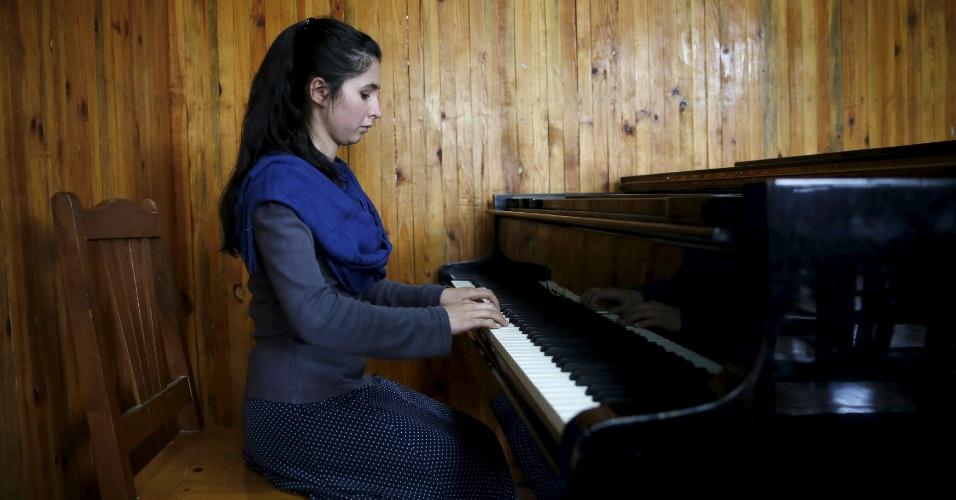 18.abr.2016 - Negin Ekhpulwak tem 19 anos e já lidera uma orquestra composta por 35 mulheres, em Cabul, no Afeganistão. É ela quem toca piano nessa foto tirada no dia 9 de abril no Instituto Nacional de Música do Afeganistão, que fica na capital afegã. No país, a atividade musical foi banida durante muitos anos durante o regime do Talibã e muitos muçulmanos conservadores desaprovam a maioria das formas de música