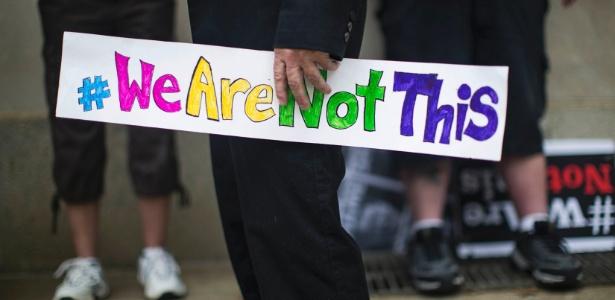 """Opositor da lei que limita banheiros a transgêneros segura cartaz com os dizeres """"não somos isso"""""""
