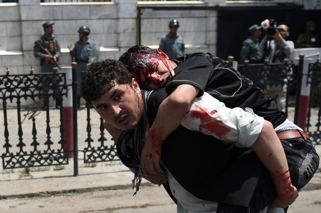 17.jun.2016 - Manifestante carrega colega ferido durante um confronto com a polícia afegã em uma manifestação contra militantes do Talibã, em Cabul. Centenas de afegãos protestaram contra o sequestros de civis no nordeste do Afeganistão