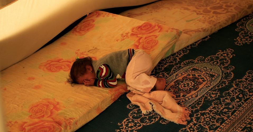 15.nov.2016 - Menina se deita em tenda de campo de refugiados que fugiram de áreas dominadas pelo Estado Islâmico no Iraque. Sara, de dois anos, nasceu sob o domínio da organização terrorista. Ela não tem documentos de identidade reconhecidos pelas autoridades iraquianas