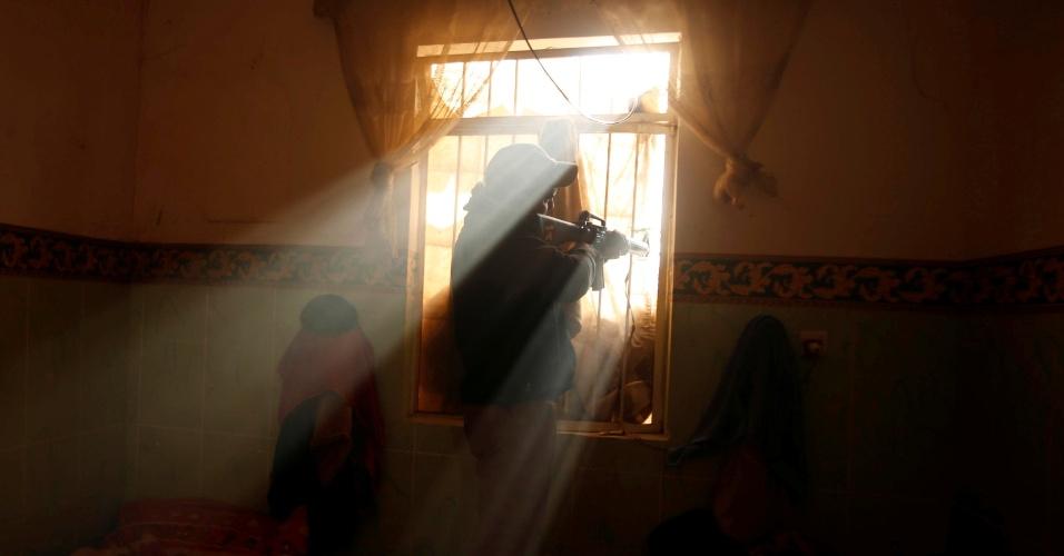 28.nov.2016 - Soldado iraquiano atira de janela em operação contra o Estado Islâmcio em Intisar, a leste de Mossul