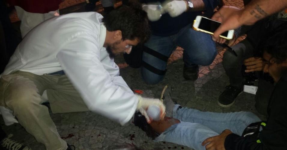 18.mai.2017 - Manifestante recebe atendimento após ser ferido na perna durante ato contra o presidente Michel Temer no Rio de Janeiro