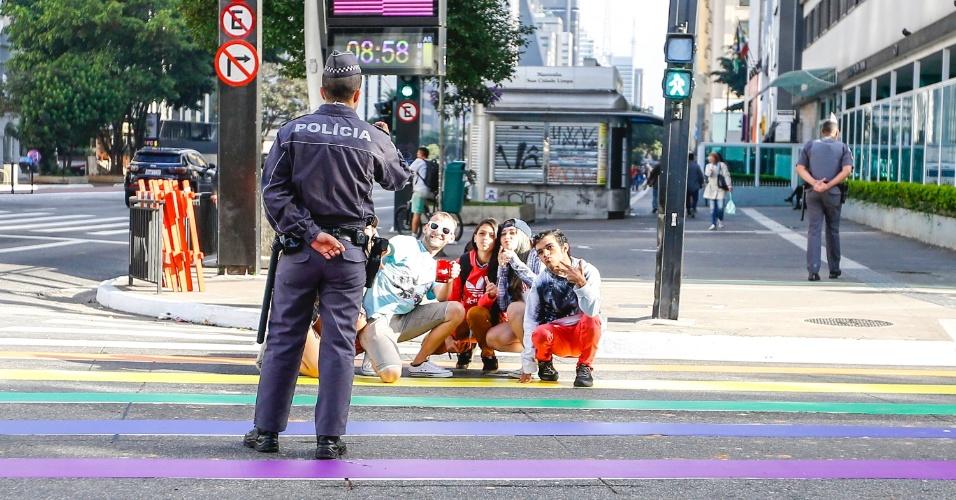 18.jun.2017 - Policial militar faz registro fotográfico de participantes da Parada Gay 2017, em São Paulo, durante a concentração do evento. O tradicional desfile em favor da diversidade começa na avenida Paulista e segue pela rua da Consolação até a praça da República, no centro da capital