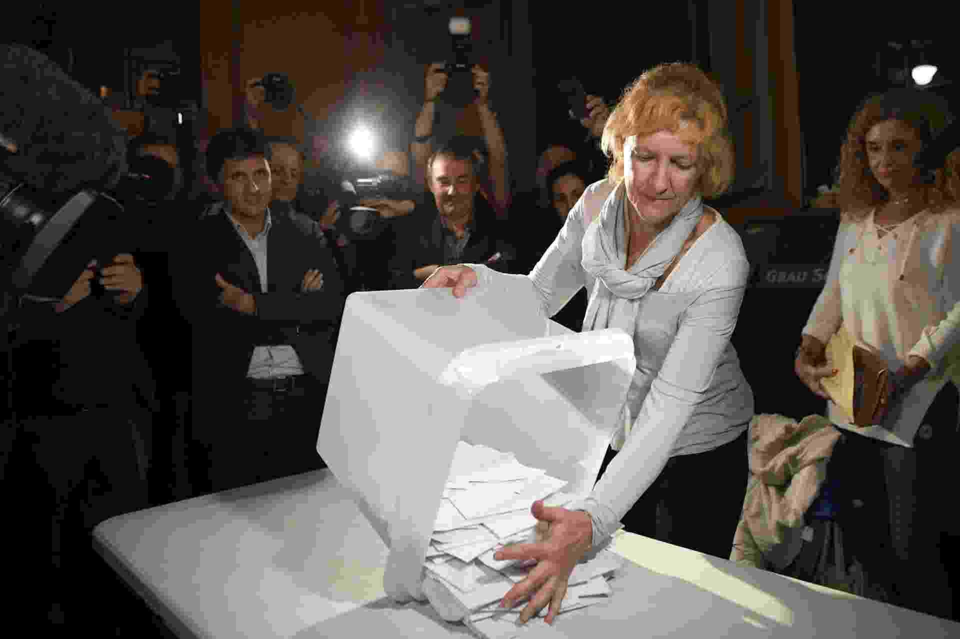 1º.out.2017 - Mulher esvazia urna para contar votos em referendo sobre a independência da Catalunha - Lluis Gene/AFP