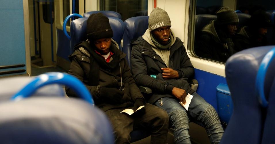 Imigrantes viajam de trem após tentarem chegar à França