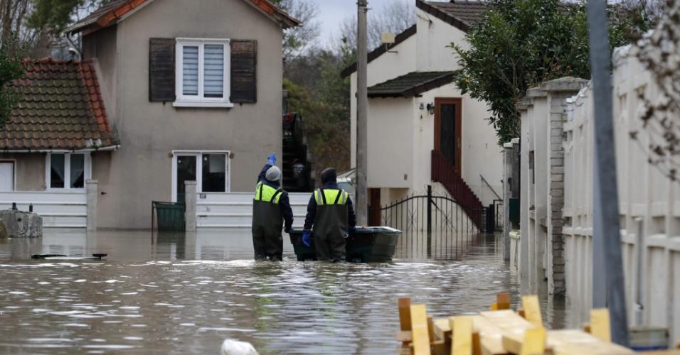 24.jan.2018 - Homens carregam uma lixeira por uma das ruas inundadas da comuna de Villeneuve-Saint-Georges, na França.