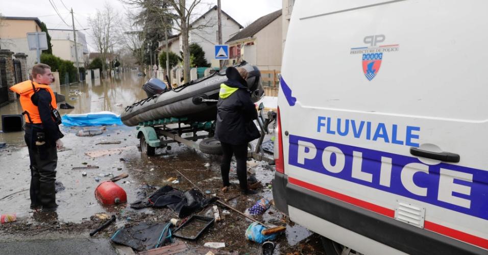 24.jan.2018 - Membros da polícia marinha francesa montam um bote inflável para poderem descer por uma rua inundada de Villeneuve-Saint-Georges, na França