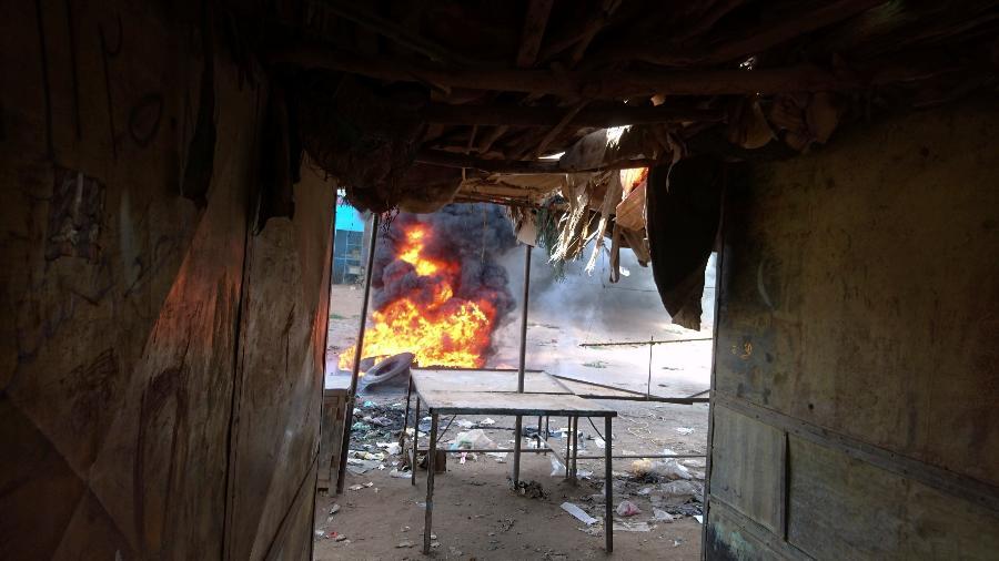 Uma fogueira é acesa ao longo da rua durante protestos contra aumentos de preços no Sudão - REUTERS/El tayeb Siddig