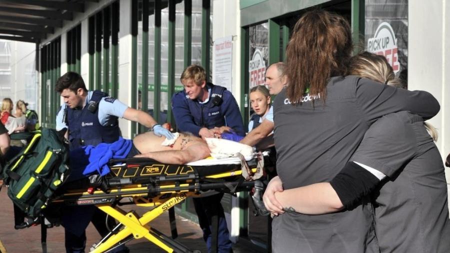 """Equipe de supermercado se abraça enquanto policiais levam vítima a uma ambulância do lado de fora de um supermercado Countdown no centro de Dunedin - Christine O""""Connor/Otago Daily Times via AP"""