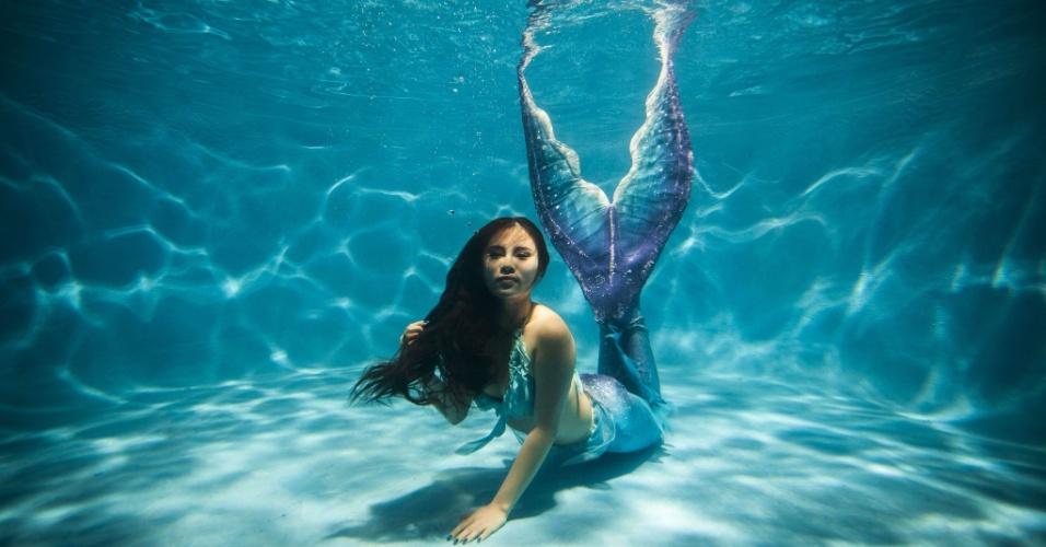 27.jul.2015 - Mulher vestida com fantasia de sereia que ela mesmo produziu posa para foto em piscina, no município  de Chongqing, na China