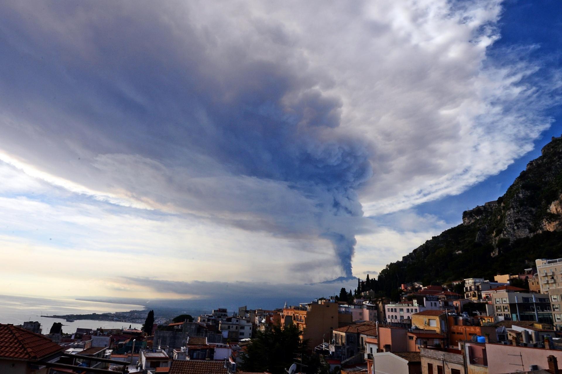 4.dez.2015 - Uma coluna de fumaça sai do vulcão Etna, visto da cidade de Taormina, na Itália. O Etna é um dos vulcões mais ativos do mundo, e fica próximo a Catania