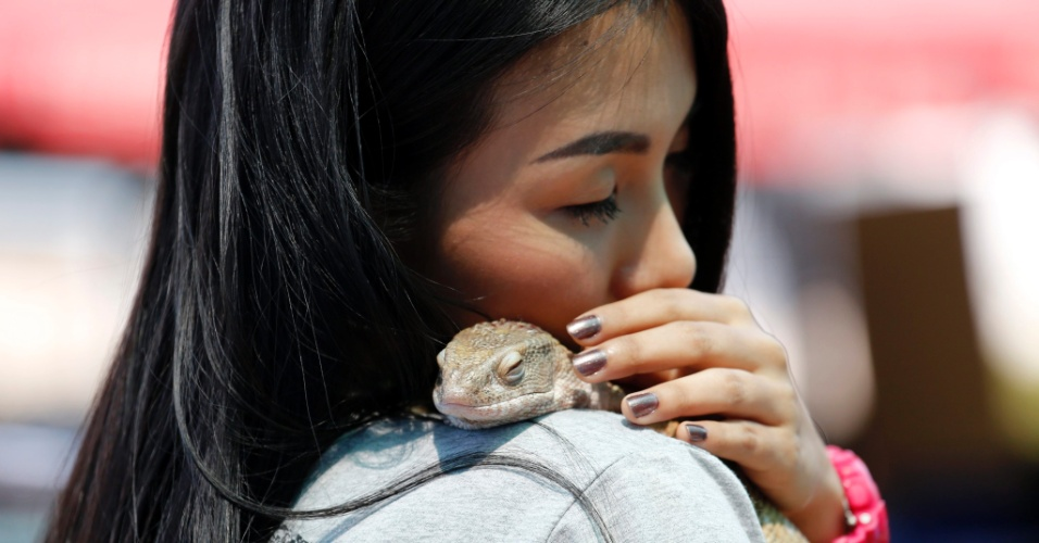 29.fev.2016 - A tailandesa Nam Monz faz carinho do seu lagarto, Savannah, de 8 meses, nativo da África, durante evento de animais de estimação exóticos na Universidade de Mahidol, em Bancoc, na Tailândia. Concursos e eventos de animais de estimação costumam ser cheios de cães e gatos. Mas, esse reúne amantes de animais exóticos criados em ambiente doméstico. Os favoritos dos tailandeses são os cães de pradaria, cobras e muitas espécies de lagartos, além de corujas e raposas. No Brasil, é proibido ter como animais de estimação muitos desses animais