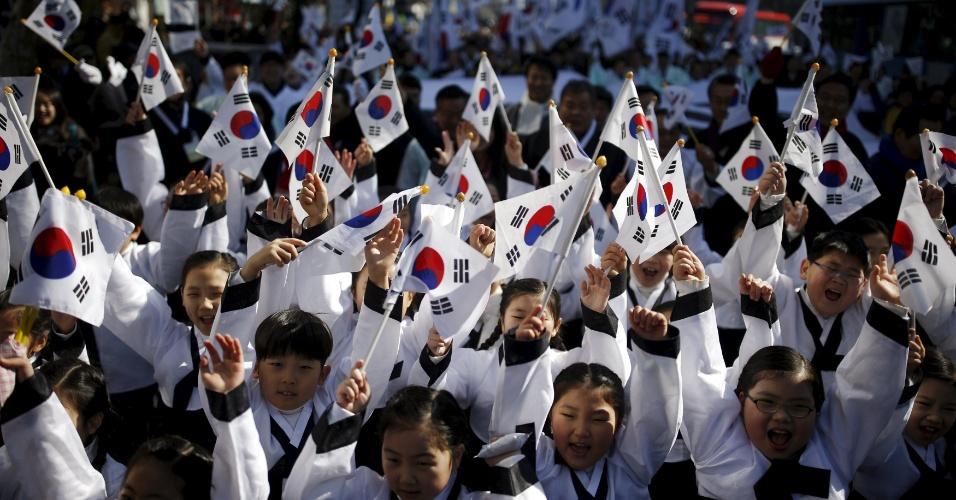 1º.mar.2016 - Vestidas com trajes tradicionais, crianças sul-coreanas agitam bandeiras nacionais durante desfile em Seul em celebração ao Dia da Declaração de Independência do país
