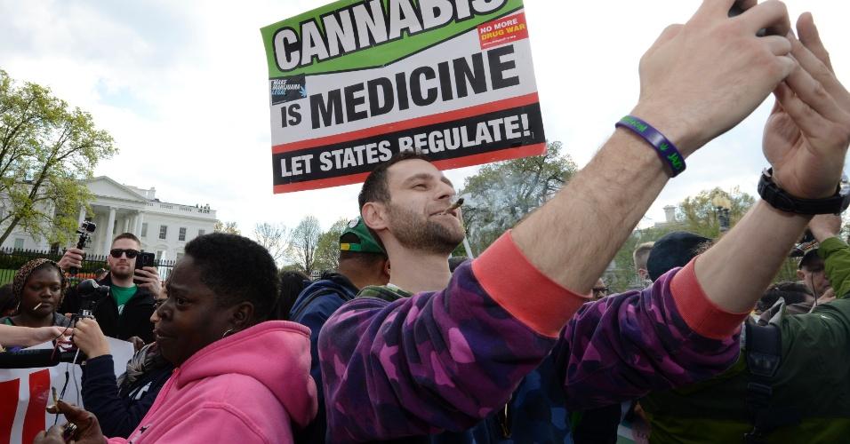 """2.abr.2016 - Manifestante tira selfie com cigarro de maconha na boca. Ao fundo, cartaz diz que a substância é um """"medicamento"""""""