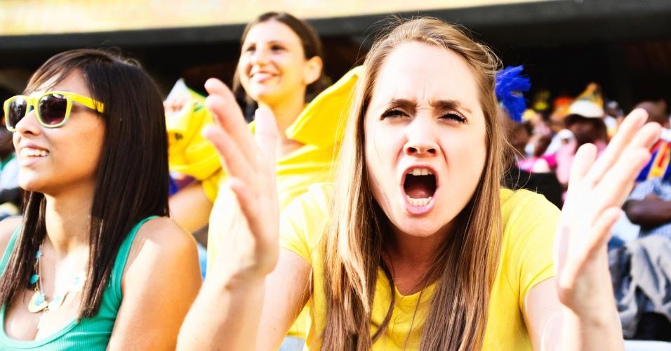 Mulher de camisa amarela esbraveja olhando para a câmera