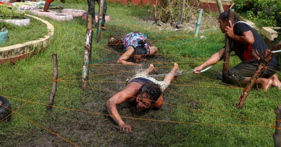 24.set.2016 - Usuários de drogas se arrastam na lama como parte de atividade de programa de reabilitação organizado pelo governo de San Fernando, no norte das Filipinas