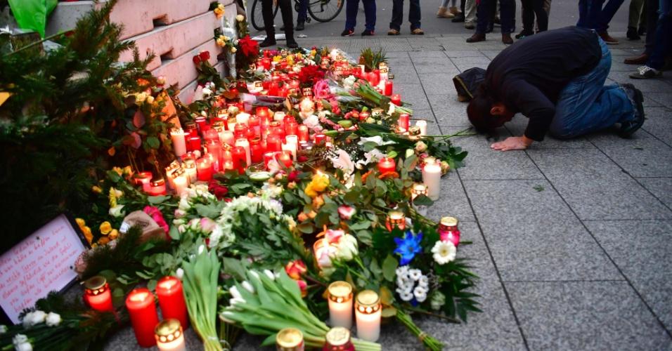 20.dez.2016 - Muçulmano reza diante de flores e velas colocados diante da Igreja Memorial do Imperador Guilherme, em Berlim, em homenagem às vítimas do ataque a um mercado de Natal ocorrido na véspera na capital da Alemanha