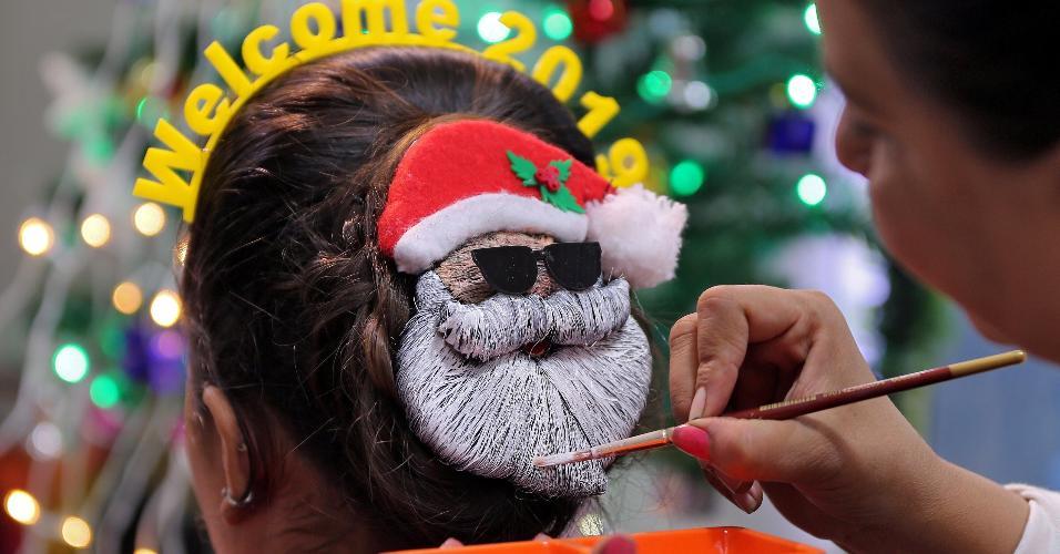 31.dez.2018 - Maquiador decora cabelo de jovem com pintura de Papai Noel em Ahmedabad, na Índia, para festa de Ano-Novo