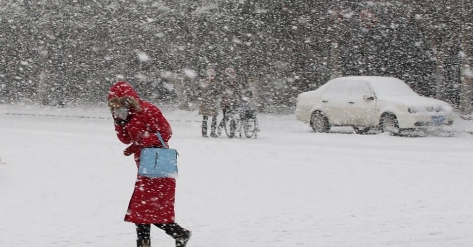 19.jan.2016 - Pedestre atravessa tempestade de neve em Yantai, na China. A temperatura pode chegar aos -12ºC durante o dia