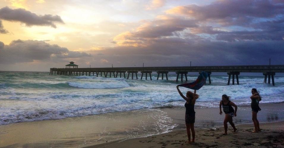 18.abr.2016 - Banhistas assistem a nascer do sol na praia de Deerfield Beach, na Flórida (EUA)