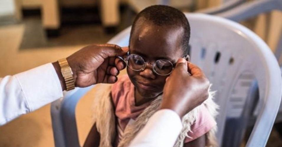 8.jul.2016 - Um médico põe os óculos em Criscent, permitindo-lhe ver o mundo com nitidez pela primeira vez