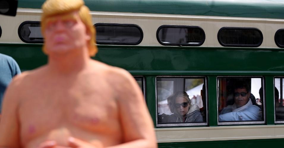 18.ago.2016 - Passageiros de trem observam a estátua de Donald Trump, em San Francisco