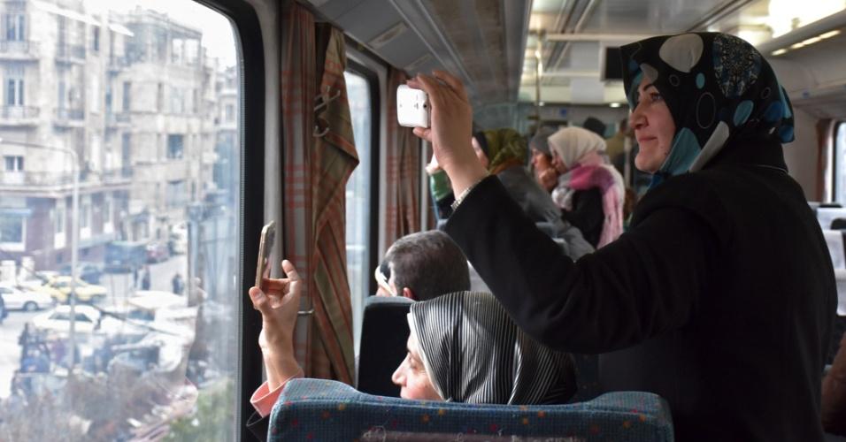 Mulheres tiram fotos de dentro de um trem durante viagem pela região leste, reconquistada pelas forças de segurança sírias. O trem voltou a circular pela região neste ano depois de quatro anos