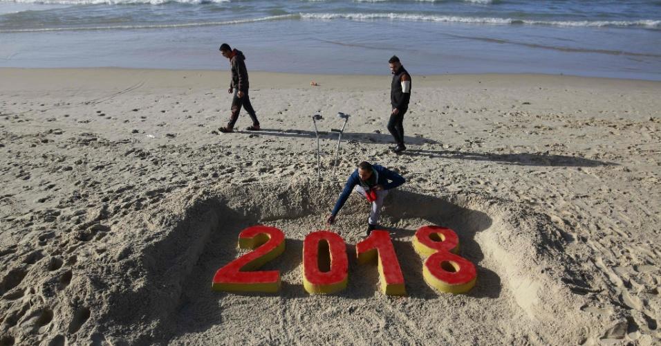 Artista palestino dá os retoques finais a sua obra na praia da Faixa de Gaza, no último dia do ano