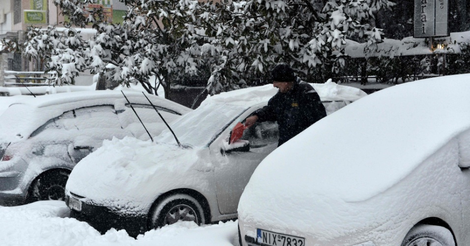 26.fev.2018 - Um homem limpa os vidros de um carro após uma forte nevasca em Hortiatis, na Grécia