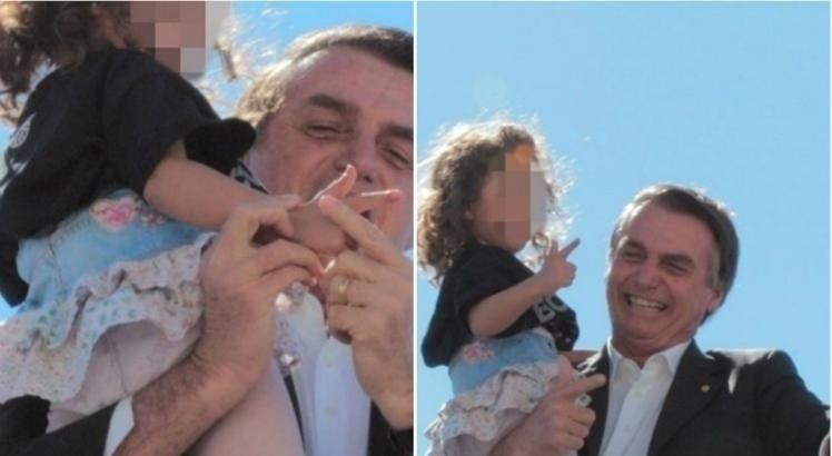 19.jul.2018 - Presidenciável Jair Bolsonaro (PSL-RJ) faz gesto de arma com as mãos de uma menina em Goiânia