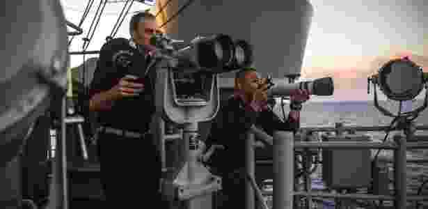 29.ago.2018 - Marinheiros da equipe de coleta de dados do porta-aviões USS Chancellorsville observam e fotografam uma fragata chinesa que os seguia em sua patrulha no mar do Sul da China - Bryan Denton/The New York Times