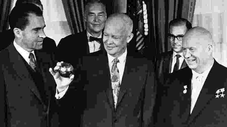 Um presente jocoso: olhado pelo premiê soviético Khrushchev (à direita) e pelo vice-presidente Richard Nixon (esquerda), Dwight Eisenhower segura uma cópia da esfera enviada à Lua a bordo da Luna 2, em 1959 - Getty Images/BBC