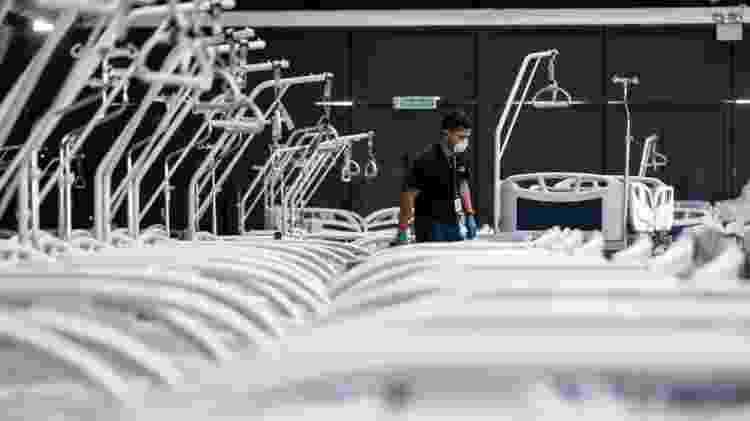 Homem de máscara em meio a leitos hospitalares - AFP via BBC - AFP via BBC