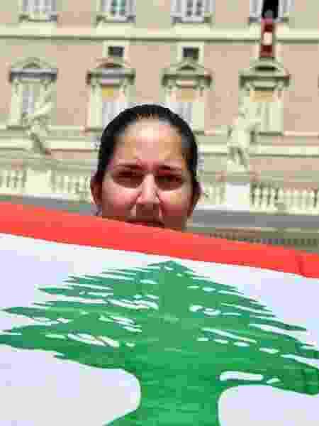 Mulher segura bandeira do Líbano enquanto esperava pelo Angelus do papa Francisco neste domingo no Vaticano - Alberto Pizzoli/AFP